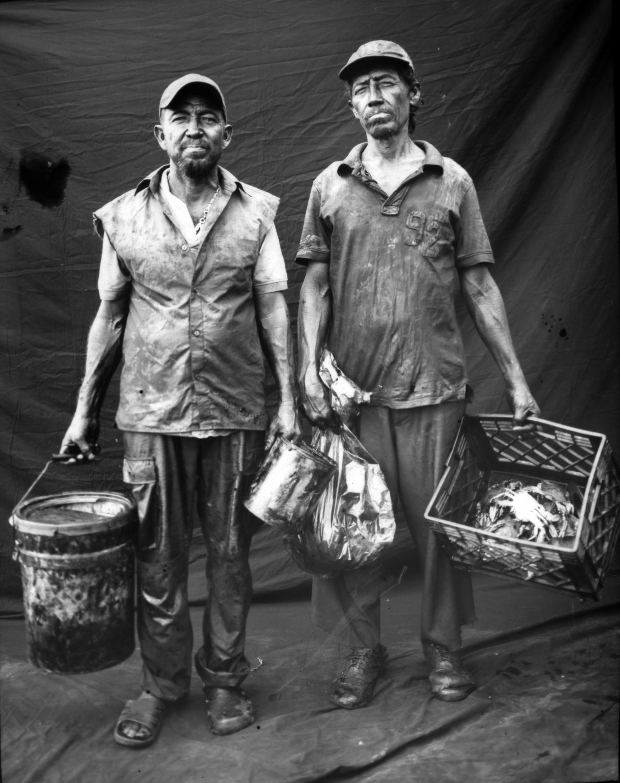 Fisherman Antonio Tello, left, poses for a portrait with his brother after harvesting crabs in oil-contaminated Lake Maracaibo in Cabimas, Venezuela. (Photo: Rodrigo Abd/AP)