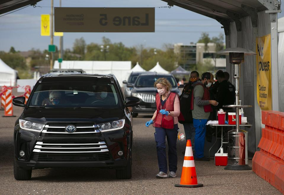 Dr. Cara Christ, director of the Arizona Department of Health Services, administers COVID-19 vaccines to educators in the parking lot at Phoenix Municipal Stadium on Feb. 1.