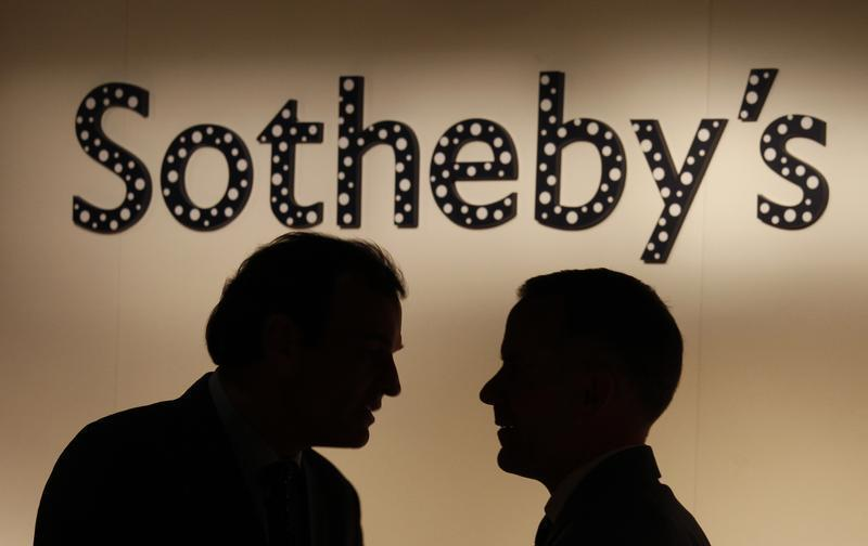 Two men chat in front of a polka dot covered Sotheby's signage, part of an installation by Japanese artist Kusama, at Sotheby's newly opened gallery in Hong Kong