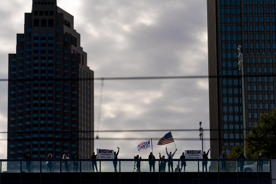 Supporters ring cow bells and wave across the train tracks during an event for Democratic presidential candidate former Vice President Joe Biden at Amtrak's Cleveland Lakefront train station, Wednesday, Sept. 30, 2020, in Cleveland, Biden is on a train tour through Ohio and Pennsylvania today. (AP Photo/Andrew Harnik)