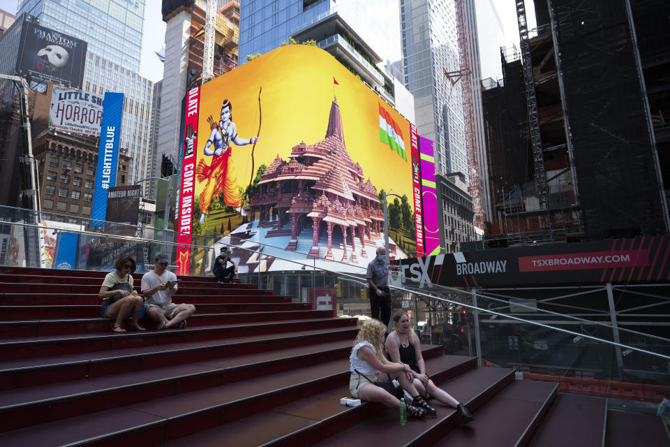 People take a break in Times Square as the imagery of the Hindu deity Ram and 3-D portraits of the proposed Hindu temple are displayed on a digital billboard, New York, Wednesday, Aug. 5, 2020, to celebrate the groundbreaking ceremony of a temple dedicated to the Hindu god Ram by Indian Prime Minister Narendra Modi in Ayodhya, in New Delhi, India. Hindus rejoiced as Modi broke ground on a long-awaited temple of their most revered god, Ram, at the site of a demolished 16th century mosque. (AP Photo/Mark Lennihan)