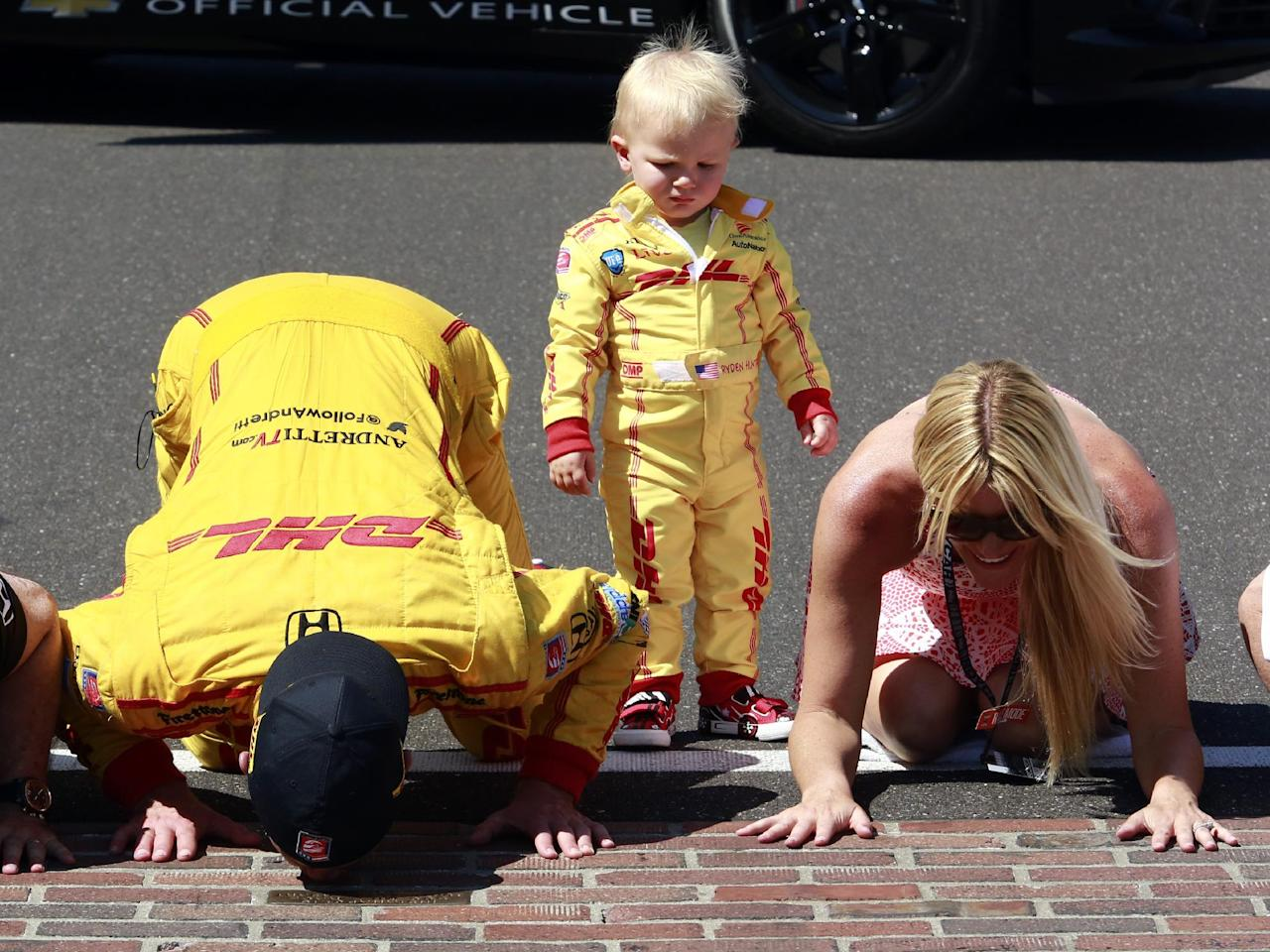 Ryan Hunter-Reay and his wife, Beccy Gordon, kiss the bricks as their son, Ryden, watches after Hunter-Reay won during the 98th running of the Indianapolis 500 IndyCar auto race at the Indianapolis Motor Speedway in Indianapolis, Sunday, May 25, 2014. (AP Photo/R Brent Smith)