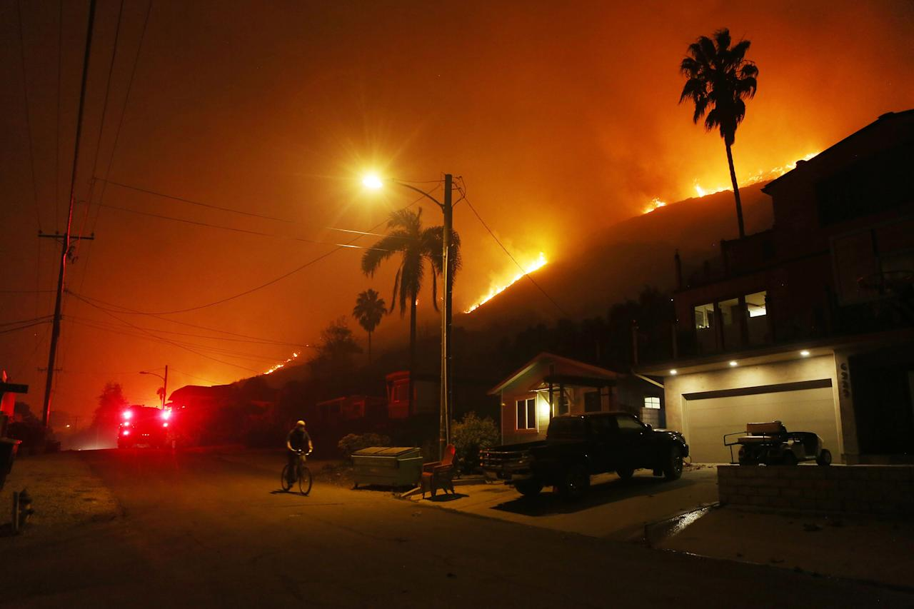 <p>A person bicycles as a section of the Thomas Fire burns on a bluff on Dec. 7, 2017 in La Conchita, Calif. (Photo: Mario Tama/Getty Images) </p>