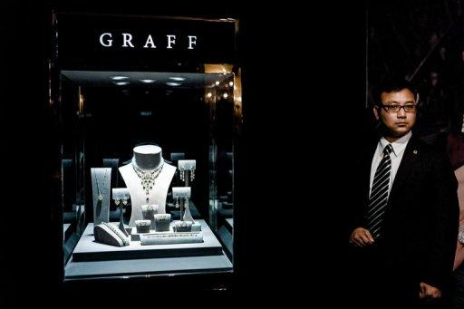 """<p>A member of security personnel is seen standing by a display of diamonds during a roadshow by Graff Diamonds in Hong Kong, on May 21. The company announced on Thursday it has decided to delay its $1.0 billion initial public offering in Hong Kong next month due to """"adverse market conditions.""""</p>"""