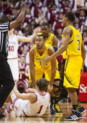 Michigan's Jon Horford (15) reacts to being called for a foul while battling for a loose ball with Indiana's Jordan Hulls (1) during the first half of an NCAA college basketball game Saturday, Feb. 2, 2013, in Bloomington, Ind. (AP Photo/Doug McSchooler)