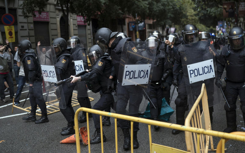 Spanish riot police removes fences thrown to them as one aims his rubber bullet rifle as they try to prevent people from reaching a voting site at a school assigned to be a polling station. (AP Photo/Felipe Dana)