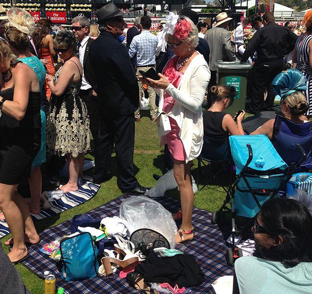 Many racegoers set up a picnic and went barefoot on the green. Source: Sophie Smith.