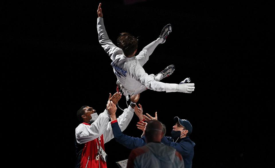 <p>France's Romain Cannone celebrates with team members on July 25 after winning in the men's epee individual gold medal fencing bout.</p>
