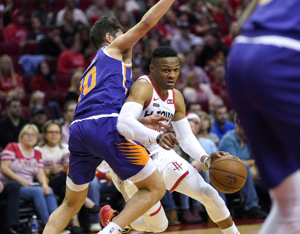Houston Rockets' Russell Westbrook, right, drives toward the basket as Phoenix Suns' Ty Jerome (10) defends during the first half of an NBA basketball game Saturday, Dec. 7, 2019, in Houston. (AP Photo/David J. Phillip)