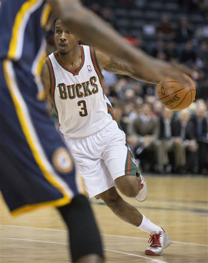 Milwaukee Bucks' Brandon Jennings drives the lane against the Indiana Pacers defense during the first half of an NBA basketball game on Wednesday, Nov. 14, 2012, in Milwaukee. (AP Photo/Tom Lynn)