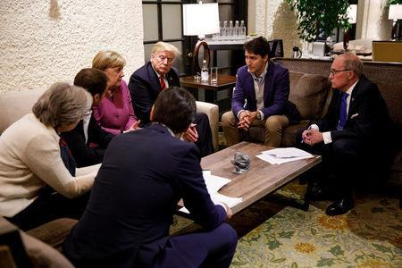 Canada's Prime Minister Justin Trudeau and G7 leaders France's President Emmanuel Macron, Germany's Chancellor Angela Merkel, Britain's Prime Minister Theresa May and U.S. President Donald Trump hold a meeting with staff on the first day of the G7 meeting in Charlevoix city of La Malbaie, Quebec, Canada, June 8, 2018. Picture taken June 8, 2018. Adam Scotti/Prime Minister's Office/Handout via REUTERS