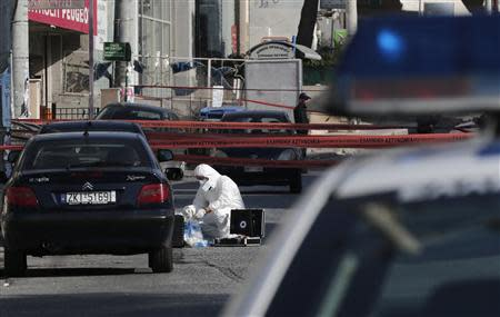 A police forensic expert searches for evidence outside the local offices of far-right Golden Dawn party, following last night's shooting, in a northern suburb of Athens November 2, 2013. REUTERS/John Kolesidis