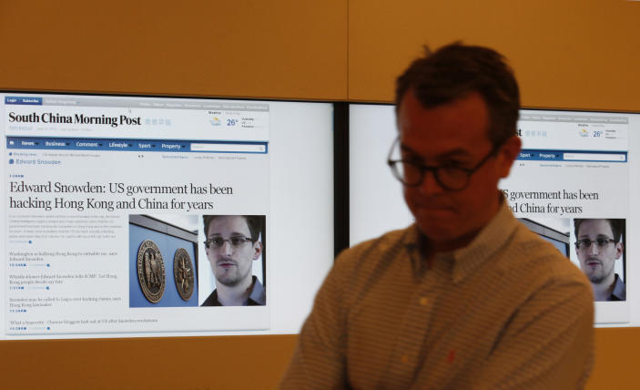 A staff member of the South China Morning Post walks past screens showing news on Edward Snowden, former CIA employee who leaked top-secret documents about sweeping U.S. surveillance programs, at its headquarters in Hong Kong Thursday, June 13, 2013. Snowden dropped out of sight after checking out of a Hong Kong hotel on Monday. The Hong Kong newspaper said it was able to locate and interview him on Wednesday. It provided brief excerpts from the interview on its website. (AP Photo/Kin Cheung)