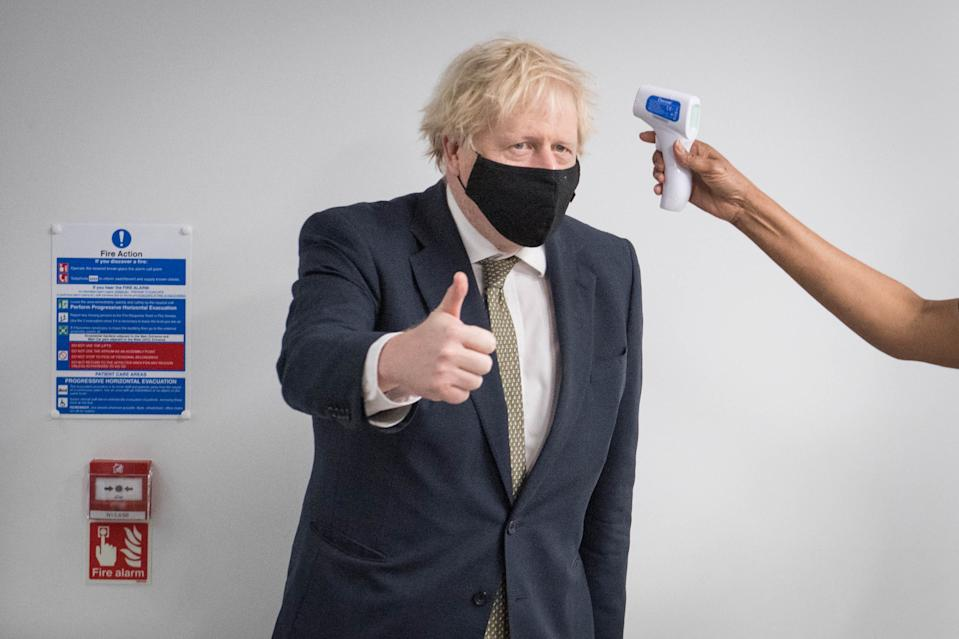 Prime Minister Boris Johnson gives a thumbs up as he has his temperature taken during a visit to view the vaccination programme at Chase Farm Hospital in north London, part of the Royal Free London NHS Foundation Trust. The NHS is ramping up its vaccination programme with 530,000 doses of the newly approved Oxford/AstraZeneca Covid-19 vaccine jab available for rollout across the UK.