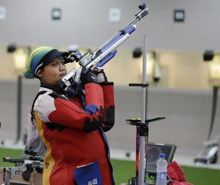 In this Thursday, July 26, 2012 photo, Malaysian shooting athlete Nur Suryani Mohamed Taibi, who is eight months pregnant, shoots during a training session for the 10-meter air rifle event, at the Royal Artillery Barracks ahead of the the start of the 2012 Summer Olympics, in London. Taibi is one of a crowd of female athletes grabbing the limelight at the 2012 London Olympics, which are quickly shaping up as a watershed for women's sports. (AP Photo/Rebecca Blackwell)