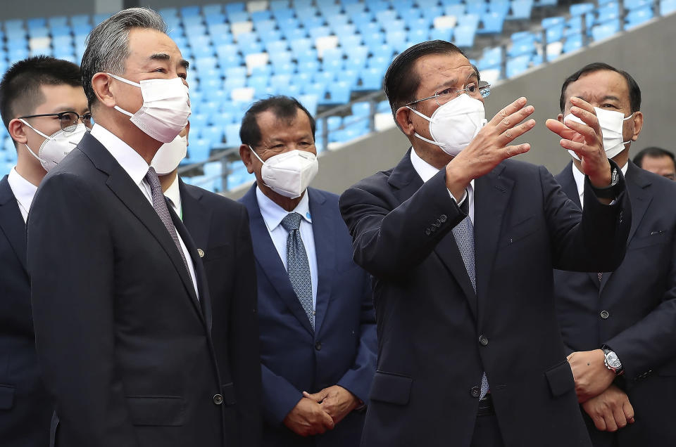 Chinese Foreign Minister Wang Yi, front left, listens to Cambodia's Prime Minister Hun Sen, front right, during a tour to the Morodok Techo National Stadium, as the stadium was handed over to the the Cambodian organizing committee of the Southeast Asian Games, in Phnom Penh, Cambodia, Sunday, Sept. 12, 2021. Wang is visiting Cambodia, where he met with Hun Sen and other officials to discuss COVID-19 and other regional issues. (Lon Jadina/Pool Photo via AP)