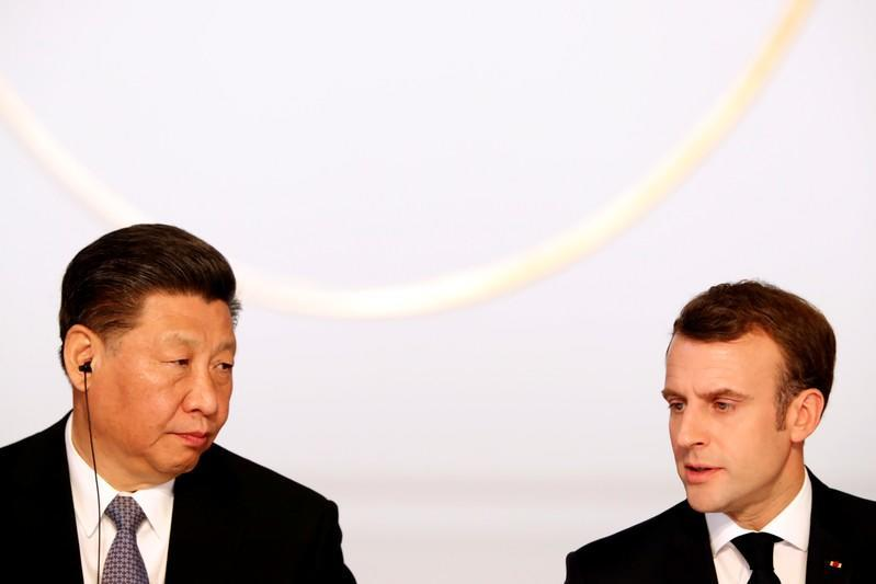 FILE PHOTO: French President Emmanuel Macron and his Chinese counterpart Xi Jinping hold a news conference with German Chancellor Angela Merkel and European Commission President Jean-Claude Juncker at the Elysee presidential palace in Paris