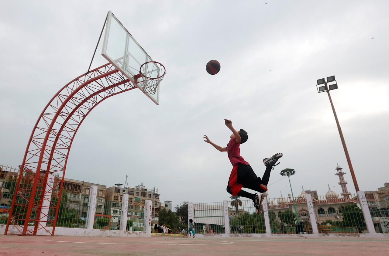 A boy plays basketball at a public park with the backdrop of monsoon clouds in Karachi, Pakistan July 14, 2017. REUTERS/Akhtar Soomro