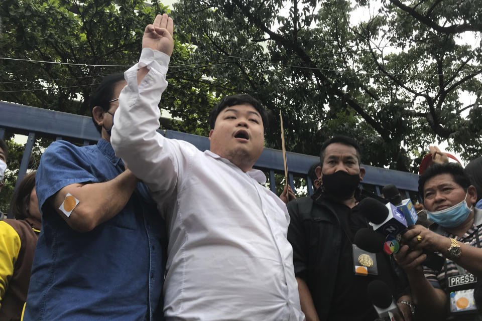 "Protest leader Parit ""Penguin"" Chiwarak raises his hand with a three-fingered salute as a symbol of resistance outside the criminal court after he was released on bail Saturday, Aug. 15, 2020 in Bangkok, Thailand. Parit was arrested by police Friday on a sedition charge in connection with a July 18 protest. (AP Photo/Busaba Sivasomboon)"