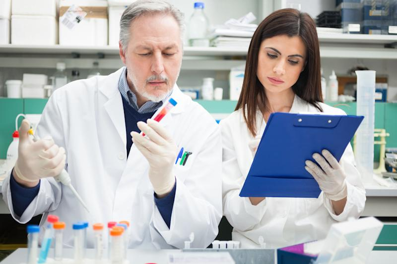 Two lab researchers in white coats examining vials and making notes.