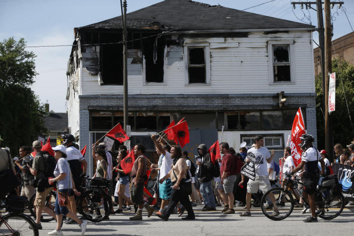 <p>Anti-Trump protesters march past a burnt-out residential building during the Republican National Convention in Cleveland on July 18, 2016. (Photo: Jim Urquhart/Reuters)</p>