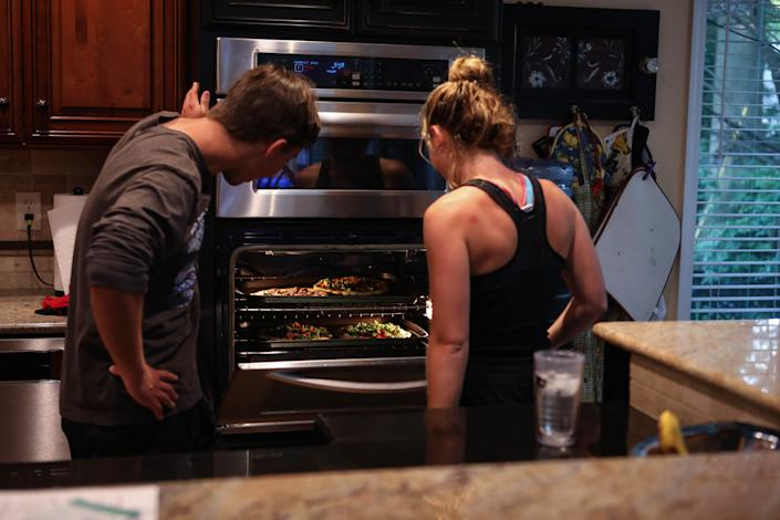 Will Rhodunda checks on the family's pizza dinner with his sister Alexa on June 12.