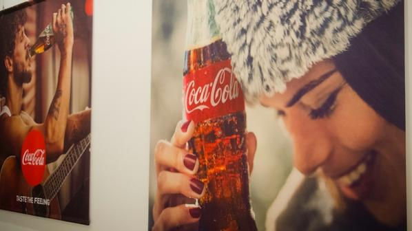 An ad for coke with a young woman holding a coke bottle to her forehead and smiling.