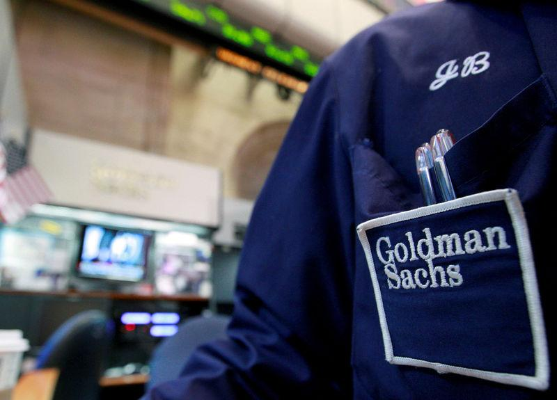 FILE PHOTO: A trader works at the Goldman Sachs stall on the floor of the New York Stock Exchange