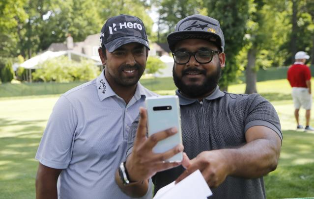 Aru Sau of Detroit, right, takes a selfie with golfer Anirban Lahiri during the Pro-Am at the Rocket Mortgage Classic golf tournament, Wednesday, June 26, 2019, in Detroit. (AP Photo/Carlos Osorio)