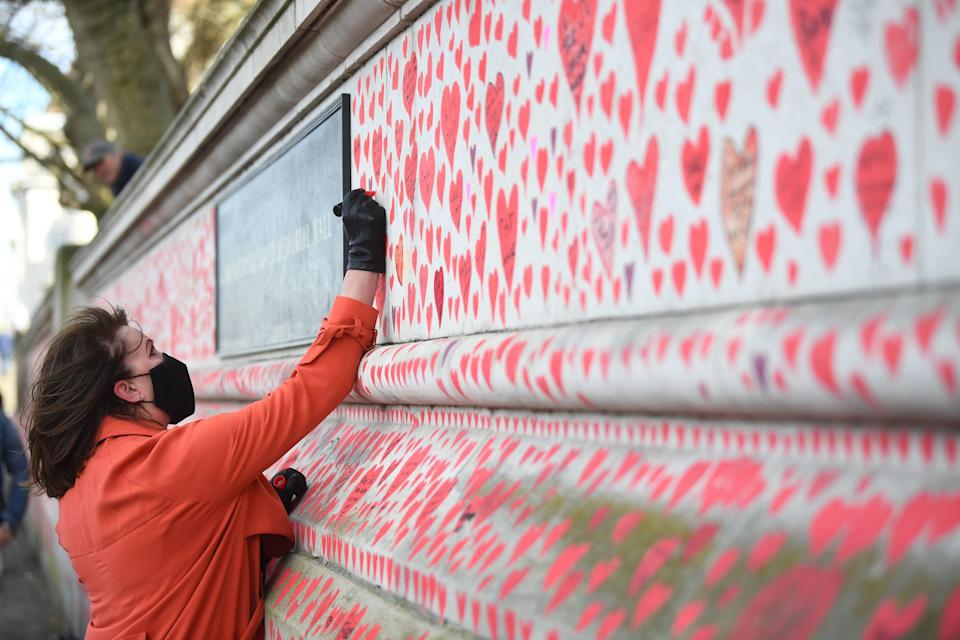 <p>A woman takes part in the final stages of painting approximately 150,000 hearts onto the National Covid Memorial Wall on the Embankment</p> (PA)