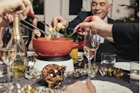 """<p>Fondue is <em>always</em> a good idea — especially when it comes to this delicious <a href=""""https://www.gettyimages.com/detail/photo/friends-eating-cheese-fondue-on-new-years-eve-royalty-free-image/642111991?adppopup=true"""" rel=""""nofollow noopener"""" target=""""_blank"""" data-ylk=""""slk:three-cheese fondue"""" class=""""link rapid-noclick-resp"""">three-cheese fondue</a> recipe! Treat your loved ones with a cozy bowl of fondue and a selection of fruits, veggies, and bread to dip to their hearts' content. And afterwards, chocolate fondue is a must for dessert, of course!</p>"""