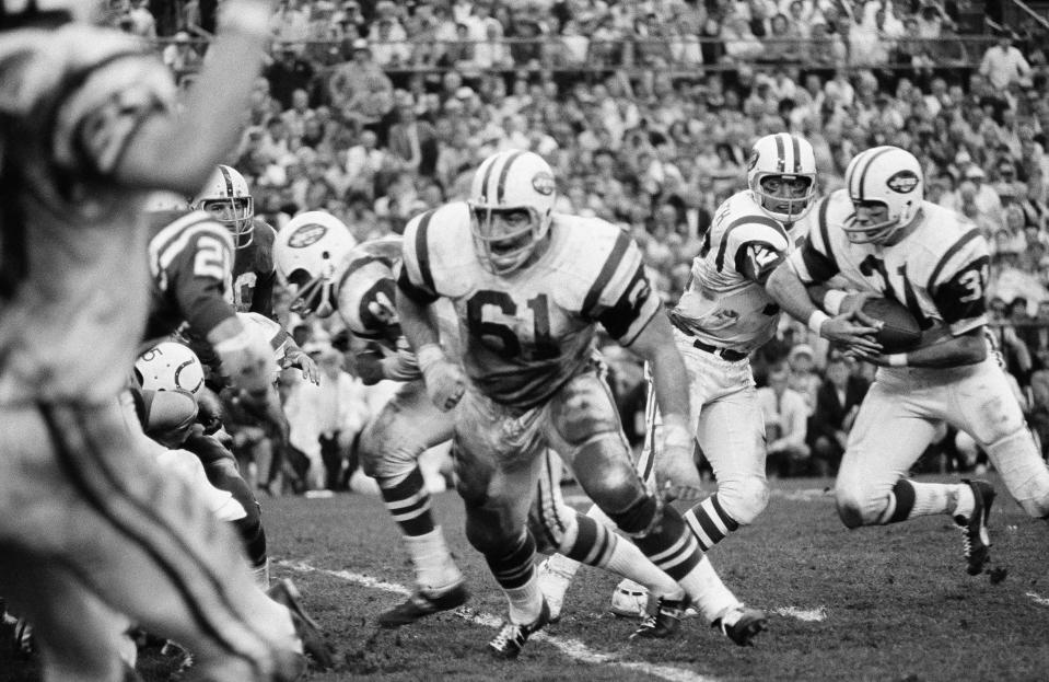 Keeping a watchful eye on a rushing defender, New York Jets quarterback Joe Namath hands off to running back Bill Mathis in Super Bowl III.