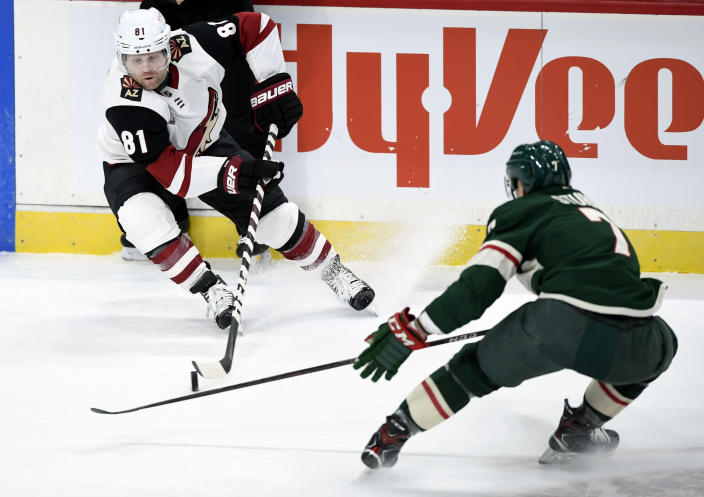 Arizona Coyotes' Phil Kessel (81) has the puck against Minnesota Wild's Nico Sturm (7), of Germany, during the first period of an NHL hockey game Sunday, March 14, 2021, in St. Paul, Minn. (AP Photo/Hannah Foslien)