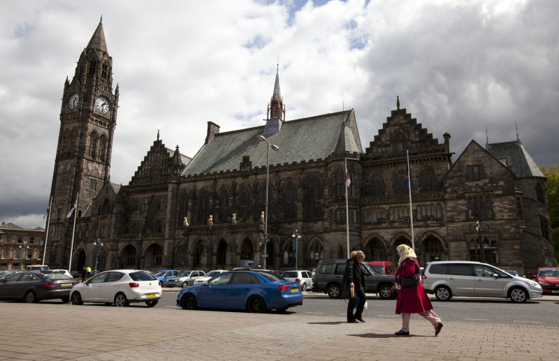 """In this Wednesday, May 16, 2012 photo, pedestrians walk past town hall in Rochdale, England. The story of the abused Rochdale girls is tragic by any measure, but it has also become explosive. Because there is no getting around its racial subtext: The girls are white, and the men who used them for sex are Asian Muslims, mostly Pakistanis raised in Britain. Louis Kushnick, founder of the race relations resource center at the University of Manchester, said it has become convenient for white residents - including those beyond the far-right movement - to blame Muslims for the sex crimes. That view overlooks all the problems that left the girls vulnerable in the first place, he says, citing a deficient school system and a government-backed child care regime riddled with neglect and abuse. And he says the prolonged economic downturn has intensified resentments, with whites and Asians competing for the same """"crap"""" jobs. """"Blaming the Muslims lets us avoid addressing these questions,"""" he says. """"Once we blame 'The Other,' we think we have an explanation that makes sense."""" (AP Photo/Jon Super)"""