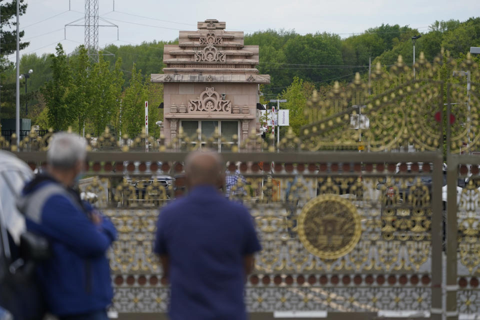 People stand near the entrance to the BAPS Shri Swaminarayan Mandir in Robbinsville Township, N.J., Tuesday, May 11, 2021. Workers from marginalized communities in India were lured to the U.S. and forced to work long hours for just a few dollars per day to help build the Hindu temple in New Jersey, according to a lawsuit filed Tuesday, May 11, 2021. The lawsuit, filed in federal court, accuses the leaders of the Hindu organization known as Bochasanwasi Akshar Purushottam Swaminarayan Sanstha, or BAPS, of human trafficking and wage law violations. (AP Photo/Seth Wenig)