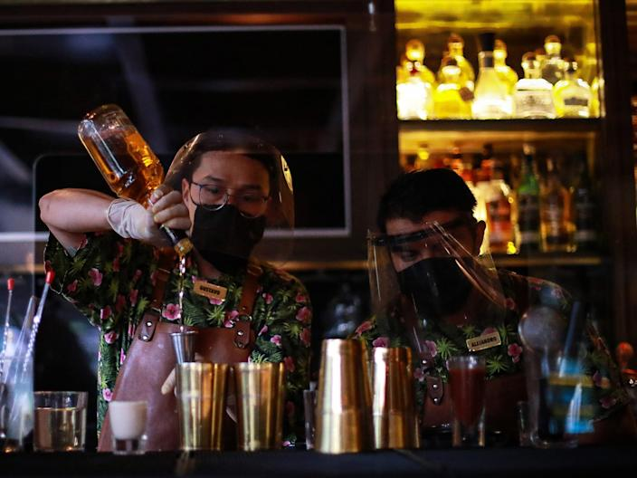 """Bartenders with face masks prepare drinks at the restaurant """"Cuerno"""" on July 03, 2020 in Mexico City. <p class=""""copyright"""">Manuel Velasquez/Getty Images</p>"""