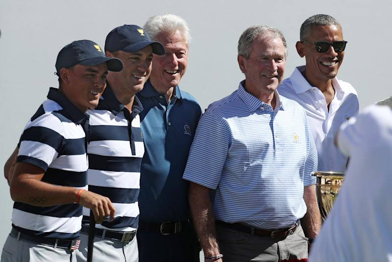 Golfers Rickie Fowler and Justin Thomas of the U.S. team pose for a photo with the three ex-presidents. (Rob Carr via Getty Images)