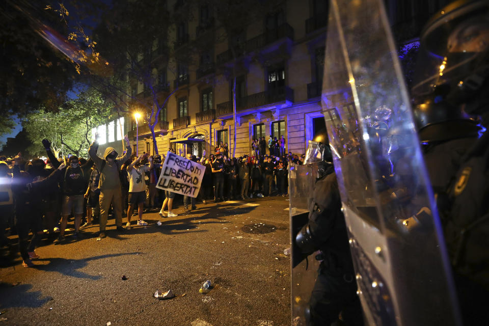 Protestors face a line of riot police outside the Spanish Government Office in Barcelona, Spain, Tuesday, Oct. 15, 2019. Spain's Supreme Court on Monday convicted 12 former Catalan politicians and activists for their roles in a secession bid in 2017, a ruling that immediately inflamed independence supporters in the wealthy northeastern region. (AP Photo/Emilio Morenatti)