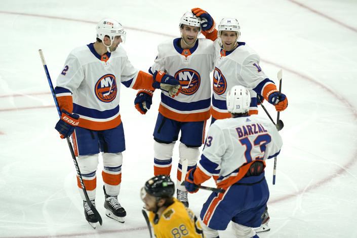 New York Islanders center Travis Zajac (14) celebrates his goal with teammates as Boston Bruins right wing David Pastrnak (88) skates by in the second period of an NHL hockey game, Thursday, April 15, 2021, in Boston. (AP Photo/Elise Amendola)