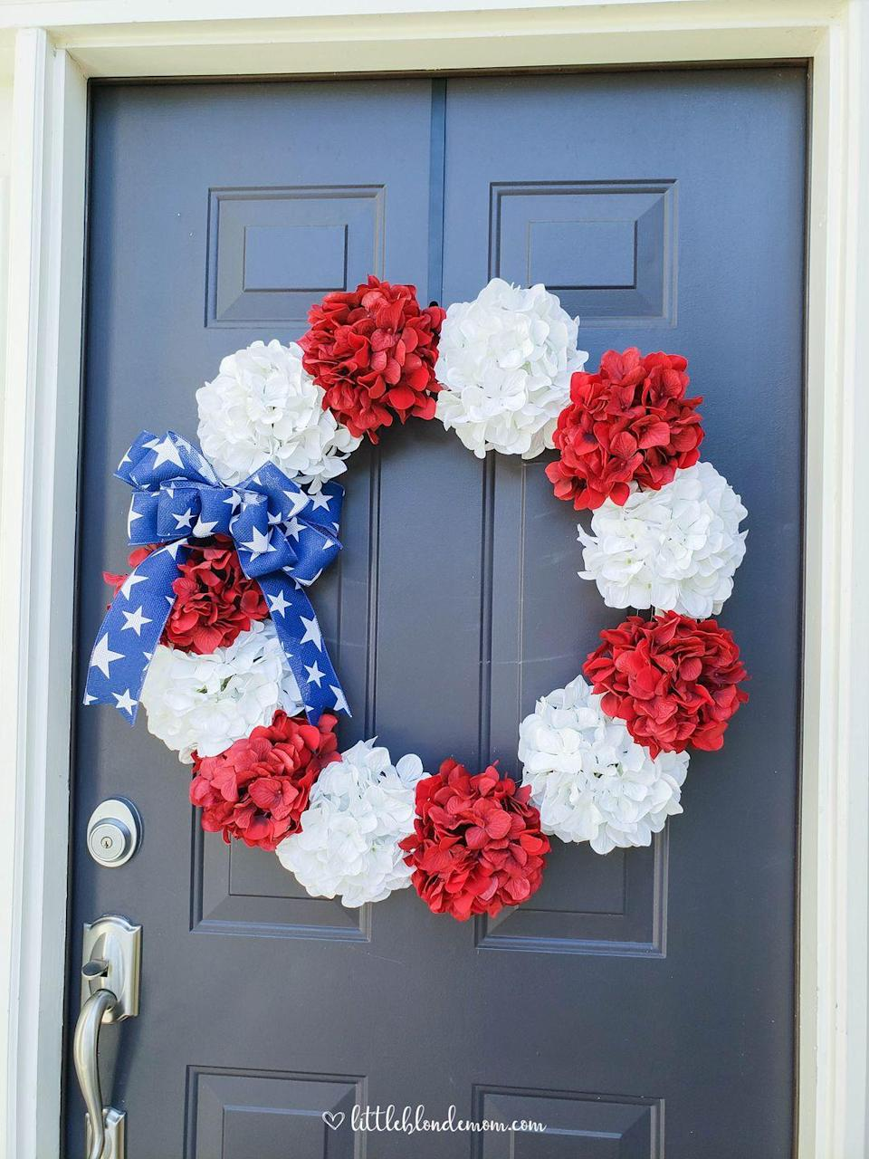 """<p>Faux flowers from Michael's take a patriotic turn with a blue-and-white star ribbon. </p><p><strong>Get the tutorial at <a href=""""http://www.littleblondemom.com/diy-patriotic-wreath/?et_fb=1"""" rel=""""nofollow noopener"""" target=""""_blank"""" data-ylk=""""slk:Little Blonde Mom"""" class=""""link rapid-noclick-resp"""">Little Blonde Mom</a>. </strong></p><p><a class=""""link rapid-noclick-resp"""" href=""""https://www.amazon.com/PPBAO-Hydrangea-Artificial-Hydrangeas-Decorations/dp/B08TVTSVW2/ref=sr_1_10?dchild=1&keywords=red+hydrangea&qid=1622038148&sr=8-10&tag=syn-yahoo-20&ascsubtag=%5Bartid%7C10050.g.4464%5Bsrc%7Cyahoo-us"""" rel=""""nofollow noopener"""" target=""""_blank"""" data-ylk=""""slk:SHOP FAUX FLOWERS"""">SHOP FAUX FLOWERS </a></p>"""