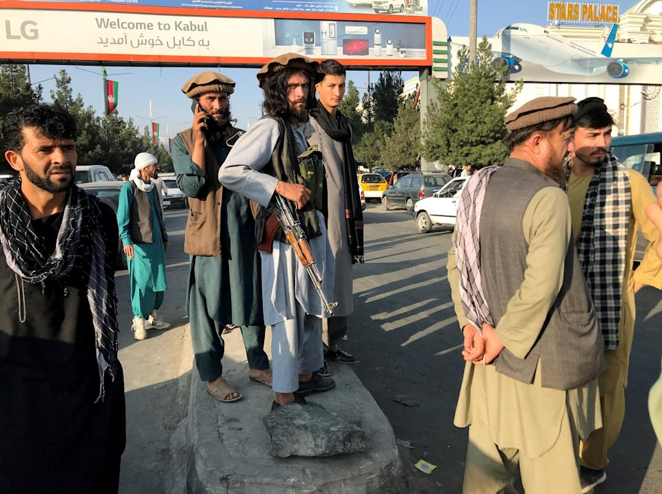 A member of Taliban (C) stands outside Hamid Karzai International Airport in Kabul, Afghanistan, August 16, 2021. REUTERS/Stringer REFILE - CORRECTING TO A MEMBER OF TALIBAN     TPX IMAGES OF THE DAY