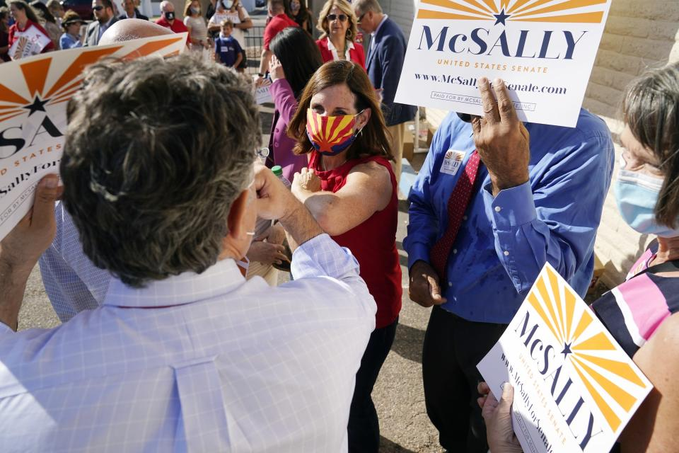 Arizona Republican Sen. Martha McSally, center, gives elbow-bumps as she campaigns at Arizona Republican Party Headquarters, Monday, Nov. 2, 2020, in Phoenix. McSally is running against Democratic candidate Mark Kelly in the election set for Tuesday. (AP Photo/Ross D. Franklin)
