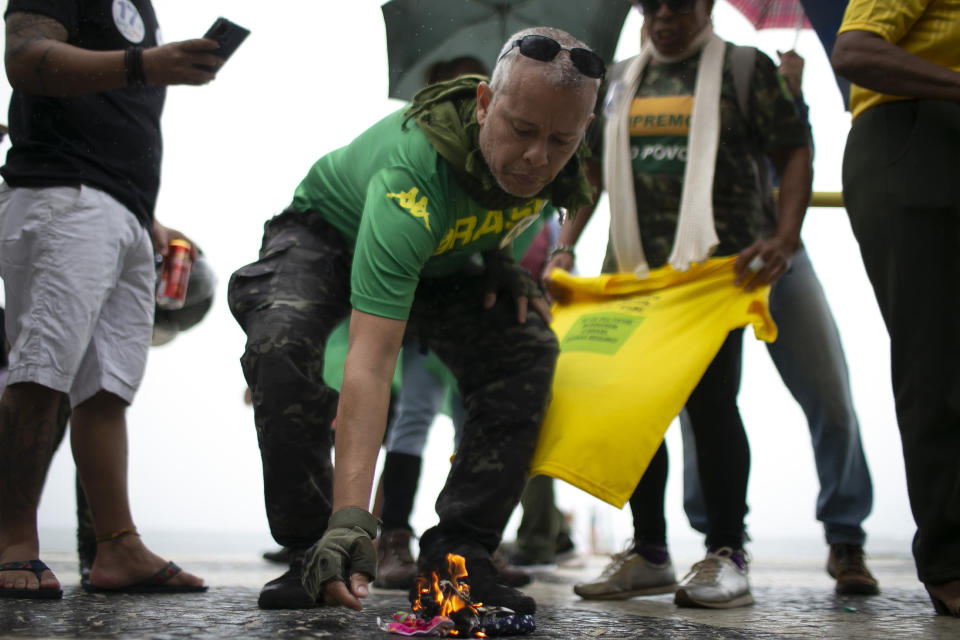 Supporters of Brazilian President Bolsonaro burn protective masks while rallying in favor of Bolsonaro's position that no one will be forced to use them and get an eventual coronavirus vaccine, on Copacabana beach in Rio de Janeiro, Brazil, Sunday, Nov. 1, 2020. Brazil has confirmed more than 159,000 deaths from the virus, the second highest in the world, behind only the U.S. (AP Photo/Bruna Prado)