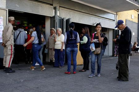 Militia officers stand guard at the entrance of a bakery as people line up to buy bread in Caracas