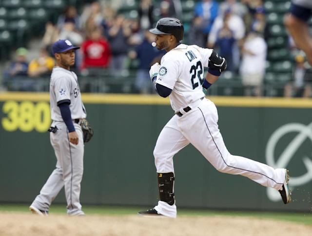 Seattle Mariners' Robinson Cano, right, blows a bubble as he rounds the bases after hitting a two-run home run during the fifth inning of a baseball game against the San Diego Padres in Seattle, Tuesday, June 17, 2014. At left is Padres third baseman Alexi Amarista. (AP Photo/Stephen Brashear)