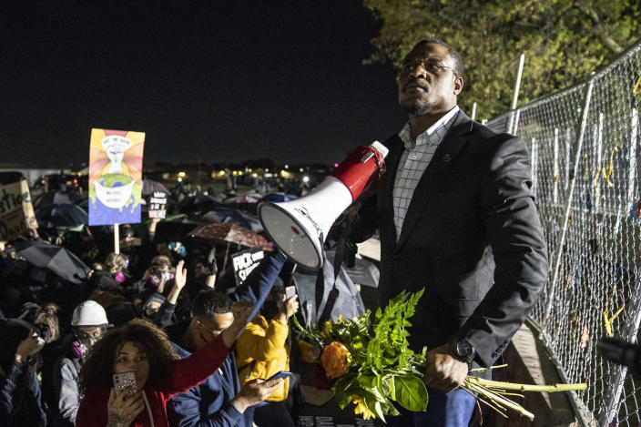 Michael Odiari leads a chant as he attempts to deescalate an altercation between demonstrators and police during a protest decrying the shooting death of Daunte Wright outside the Brooklyn Center Police Department, Friday, April 16, 2021, in Brooklyn Center, Minn. (AP Photo/John Minchillo)