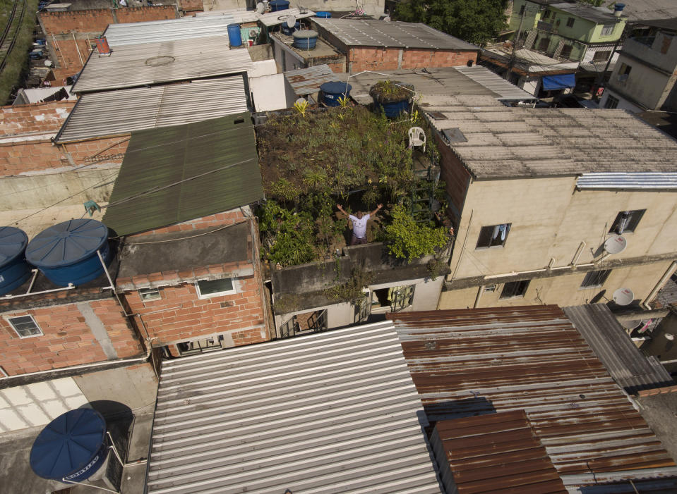"In this Jan.10, 2020 photo, Luis Cassiano shows his green roof at his home in Arara Park favela, Rio de Janeiro, Brazil. ""I think people will, one day, really wind up joining. We'll need it. Just look at the heat of all those roofs together!"" (AP Photo/Renato Spyrro)"