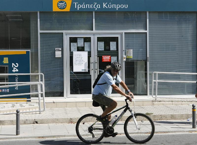 A man passes with a bicycle outside from a branch of Bank of Cyprus in Nicosia, Monday, July 29, 2013. Cyprus' government says depositors at the bailed-out country's largest lender will lose a total of 47.5 percent of their savings over 100,000 euros. Losses were initially put at 37.5 percent. Another 22.5 percent remained tied up until the lender's total recapitalization needs were calculated and announced Tuesday by government spokesman Victoras Papadopoulos. The money will be used to boost the Bank of Cyprus' capital buffers. In exchange, depositors will get shares in the bank.(AP Photo/Philippos Christou)