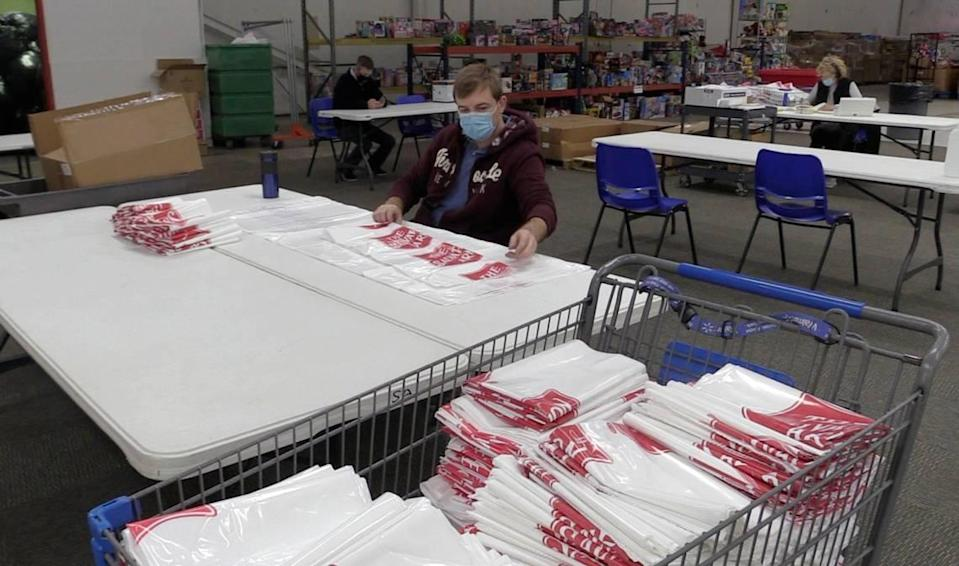 Volunteer Serge Divachuk folds family gift bags at The Salvation Army's Christmas Center on Thursday, November 19, 2020.