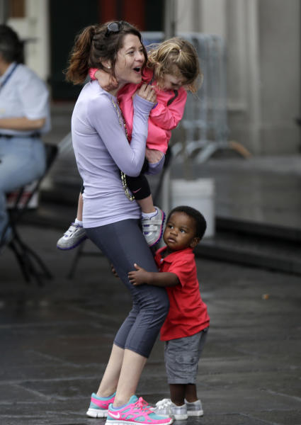 Kyron Dowden, 16 months, of Slidell, La., hugs the legs of Mary Munson-Ott, of Washington DC, as she dances to live music with her daughter Deirdre Ott, 2, on the first day of the annual French Quarter Festival in New Orleans, Thursday, April 11, 2013. French Quarter Festival, which turns 30 this year, runs through Sunday and showcases Louisiana food and music on stages strung throughout the historic neighborhood, including Jackson Square, the French Market, along narrow streets and on the Mississippi riverfront. The lineup includes Irma Thomas, trumpeter Kermit Ruffins, Cajun fiddler Amanda Shaw, the Dirty Dozen Brass Band and about 250 other acts. (AP Photo/Gerald Herbert)
